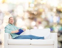 Smiling man lying on sofa with book Stock Photos