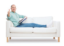 Smiling man lying on sofa with book Stock Photography