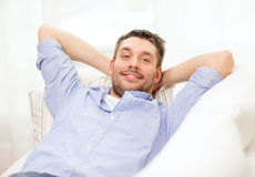Smiling man lying on sofa at home Stock Photography