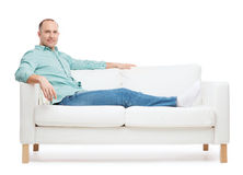 Smiling man lying on sofa Royalty Free Stock Image