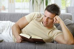 Smiling man lying on sofa reading Stock Image