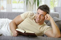 Smiling man lying on sofa reading Royalty Free Stock Images