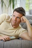 Smiling man lying on sofa watching television Stock Images