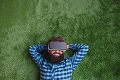 Smiling man lying in VR helmet stock images