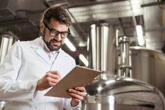 Smiling man making notes at beer factory Royalty Free Stock Photos