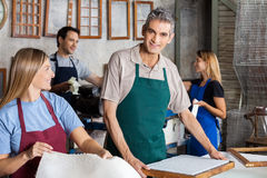 Smiling Man Making Papers With Colleagues In Royalty Free Stock Image