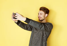 Smiling man making selfie photo over yellow background Royalty Free Stock Photography