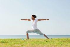 Smiling man making yoga exercises outdoors Stock Images