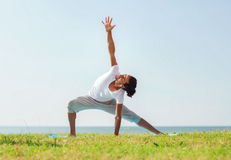 Smiling man making yoga exercises outdoors Stock Image