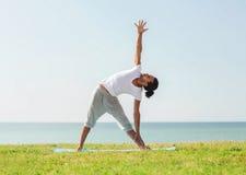 Smiling man making yoga exercises outdoors Royalty Free Stock Photos