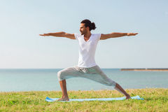 Smiling man making yoga exercises outdoors Royalty Free Stock Image