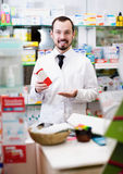 Smiling man medicine offer showing right drug. In pharmacy Royalty Free Stock Images