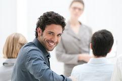 Smiling man at meeting. Satisfied businessman looking at camera during a business conference Royalty Free Stock Photography
