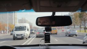 Smiling man in a mirror while driving car on a busy road in a city. Handsome mans face. Traveling by car. Traveling by car. Smiling man in a mirror while stock footage