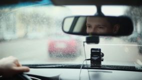 Smiling man in mirror while driving car in a city. Handsome mans face. Raindrops on the front window. Traveling by car. Traveling by car. Smiling man in a stock video