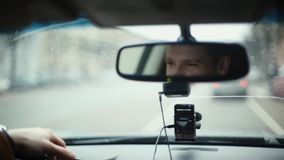 Smiling man in mirror while driving car in a city. Handsome mans face. Raindrops on the front window. Traveling by car. Traveling by car. Smiling man in a stock video footage