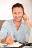 Smiling man with mobile phone. Closeup of man working at home Stock Photos