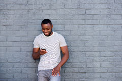 Smiling man with mobile phone leaning on brick wall. Portrait of smiling man with mobile phone leaning on brick wall Royalty Free Stock Image