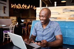 Smiling man with a mobile phone sitting at cafe using laptop Stock Photo