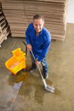 Smiling man moping warehouse floor. Portrait of smiling man moping warehouse floor Royalty Free Stock Images