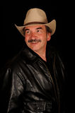 Smiling man with moustache. Studio portrait of a smiling middle-aged man with a moustache resembling Burt Reynolds, wearing a tan hat and black leather jacket royalty free stock images