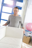 Smiling man moving sofa in living room Stock Image