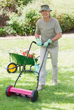 Smiling man mowing lawn Stock Image