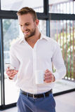 Smiling man with mug and smartphone Royalty Free Stock Photography