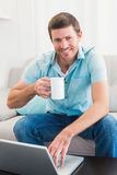 Smiling man with a mug using a laptop Stock Photography
