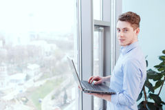 Smiling man with notebook in front of window Royalty Free Stock Photos