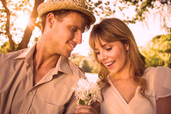 Smiling man offering his girlfriend a white flower in the park Stock Images