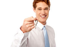 Smiling man offering house key Royalty Free Stock Image