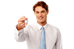 Smiling man offering house key Royalty Free Stock Photos