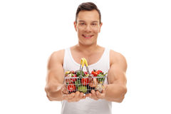 Smiling man offering a small shopping basket. Full of fruits and vegetables isolated on white background Stock Image