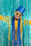 Smiling man with open arms. Brazilian wears a top hat, sunglasse. Caucasian man is holding open arms and smiling. Brazilian is wearing blue top hat, yellow Stock Photography