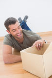 Smiling man open a moving box at home Royalty Free Stock Photo