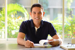 Smiling man opening book on the table Royalty Free Stock Photo
