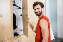 Smiling man opening locker Stock Photos