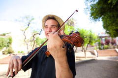 Smiling man outside playing violin Stock Images
