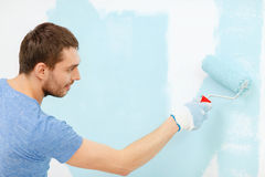 Smiling man painting wall at home. Repair, building and home concept - smiling man painting wall at home stock image