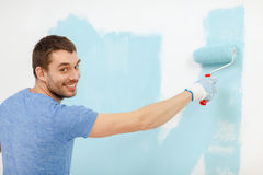 Smiling man painting wall at home. Repair, building and home concept - smiling man painting wall at home royalty free stock photos