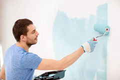 Smiling man painting wall at home. Repair, building and home concept - smiling man painting wall at home stock photo