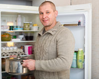 Smiling man with pan near fridge Royalty Free Stock Photography