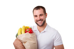 Smiling man with paper bag full of vegetables Stock Photo