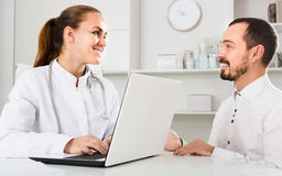 Smiling man patient with woman doctor Stock Image