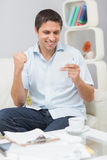 Smiling man paying his bills at home Stock Images