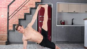 Smiling man with perfect slim body practicing yoga exercise at home looking at camera full shot. Calmness pleased male yogi training indoor enjoying healthy stock video footage