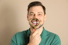 Smiling man with perfect teeth and magnifier. On color background royalty free stock images