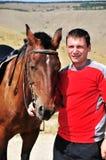 Smiling man petting his horse stock image