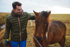 Smiling Man Petting Horse Stock Photography
